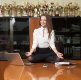 Young beautiful lady making yoga. Young beautiful lady in office sitting on the table in yoga pose and smiling with winner cups on background Stock Photography