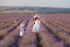 Young beautiful lady mother with lovely daughter walking on the lavender field on a weekend day in wonderful dresses and hats. Royalty Free Stock Images