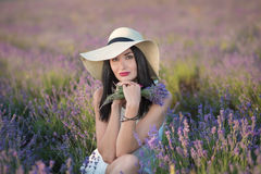 Young beautiful lady mother with lovely daughter walking on the lavender field on a weekend day in wonderful dresses and hats. Young beautiful lady mother with stock images