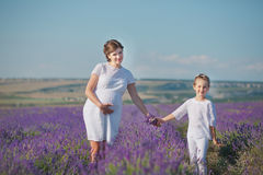 Young beautiful lady mother with lovely daughter walking on the lavender field on a weekend day in wonderful dresses and hats. Royalty Free Stock Image