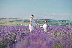 Young beautiful lady mother with lovely daughter walking on the lavender field on a weekend day in wonderful dresses and hats. Stock Images