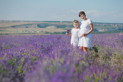 Young beautiful lady mother with lovely daughter walking on the lavender field on a weekend day in wonderful dresses and hats. Royalty Free Stock Photos