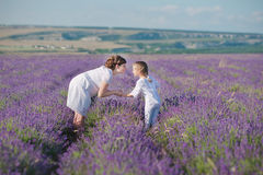 Young beautiful lady mother with lovely daughter walking on the lavender field on a weekend day in wonderful dresses and hats. Stock Photos