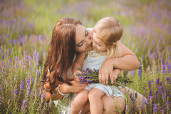 Young beautiful lady mother with lovely daughter walking on the lavender field on a weekend day in wonderful dresses and hats. Royalty Free Stock Photography
