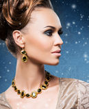 Young and beautiful lady in precious jewelry on the snow Royalty Free Stock Image