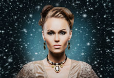 Young and beautiful lady in precious jewelry on the snow Royalty Free Stock Photo