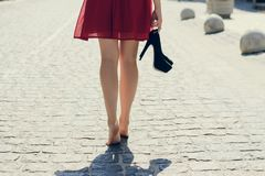 Young beautiful lady in red dress, with black high-heels in hand. Walking along the street barefoot; view from back, close up photo of woman`s legs Stock Photo