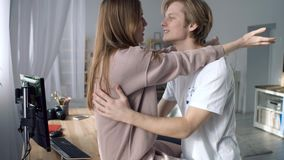 Strong first love. A young beautiful lady is sitting on the table. Her boyfriend is standing in front of her and whispering words of love stock footage