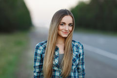 Young beautiful lady smiling outside in evening light on the forest road. Young beautiful woman smiling outside in evening light on the forest road Royalty Free Stock Photography