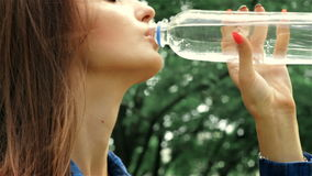 Young beautiful lady standing and drinking water. Young beautiful lady standing on the street and drinking water, close-up stock video footage