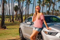 Young beautiful lady standing by the silver Ford Royalty Free Stock Photography