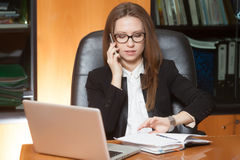 Young beautiful lady talking by phone. Young beautiful brunette woman in eyeglasses sitting in the black leather chair with laptop talking by cellphone Stock Image