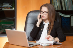 Young beautiful lady talking by phone. Young beautiful brunette woman in eyeglasses sitting in the black leather chair with laptop talking by cellphone Stock Photo