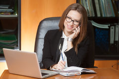 Young beautiful lady talking by phone. Young beautiful brunette woman in eyeglasses sitting in the black leather chair with laptop talking by cellphone and Stock Photography