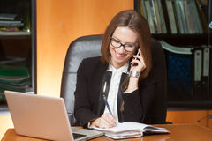 Young beautiful lady talking by phone. Young beautiful brunette woman in eyeglasses sitting in the black leather chair with laptop talking by cellphone and Royalty Free Stock Photo