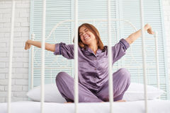 Young beautiful lady wakes up and does morning stretching sittin Royalty Free Stock Image