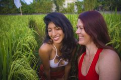 Young beautiful latin girl and her attractive red hair girlfriend both women enjoying Summer holidays together walking on rice. Field smiling happy relaxed in royalty free stock image