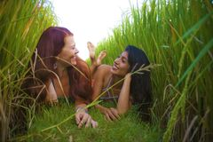 Young beautiful latin girl and her attractive red hair girlfriend both women enjoying Summer holidays together walking on rice. Field smiling happy relaxed in royalty free stock photos