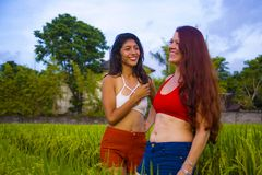 Young beautiful latin girl and her attractive red hair girlfriend both women enjoying Summer holidays together walking on rice. Field smiling happy relaxed in stock photo