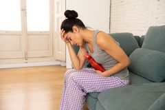 Young sad attractive woman having painful stomachache from period pain and menstrual cramps. Young beautiful latin hispanic woman in painful expression suffering stock photos