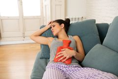 Young sad attractive woman having painful stomachache from period pain and menstrual cramps. Young beautiful latin hispanic woman in painful expression suffering stock images