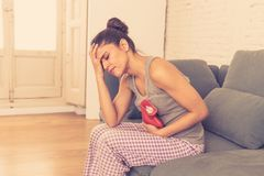 Young sad attractive woman having painful stomachache from period pain and menstrual cramps. Young beautiful latin hispanic woman in painful expression suffering royalty free stock photos