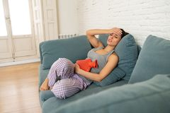Young sad attractive woman having painful stomachache from period pain and menstrual cramps. Young beautiful latin hispanic woman in painful expression suffering royalty free stock photo
