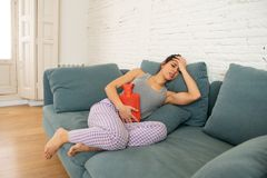 Young sad attractive woman having painful stomachache from period pain and menstrual cramps. Young beautiful latin hispanic woman in painful expression suffering royalty free stock photography