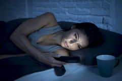 Young beautiful Latin woman on bed late at night texting using mobile phone tired falling sleep Stock Photos