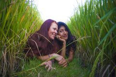 Young beautiful latin woman and her attractive red hair girlfriend both girls enjoying Summer holidays together on rice field. Young beautiful latin women and stock photos