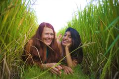 Young beautiful latin woman and her attractive red hair girlfriend both girls enjoying Summer holidays together on rice field. Young beautiful latin women and royalty free stock photos