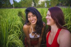 Young beautiful latin woman and her attractive red hair girlfriend both girls enjoying Summer holidays together walking on rice. Young beautiful latin women and stock image