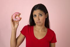 Young beautiful latin woman in red with pink sugar donut thinking and feeling guilty after biting. Background in sweet abuse and addiction and unhealthy stock image