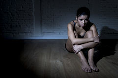 Young beautiful Latin woman or teen girl sitting sad and alone in edgy darkness feeling depressed. And desperate in mental and nutrition disorder concept Stock Photos