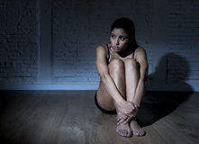 Young beautiful Latin woman or teen girl sitting sad and alone in edgy darkness feeling depressed. And desperate in mental and nutrition disorder concept Royalty Free Stock Photography