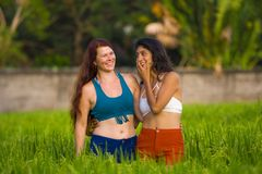 Young beautiful latin woman and her attractive red hair girlfriend both girls enjoying Summer holidays together walking on rice. Young beautiful latin women and royalty free stock photo