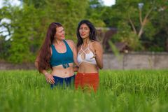 Young beautiful latin woman and her attractive red hair girlfriend both girls enjoying Summer holidays together walking on rice. Young beautiful latin women and stock photos