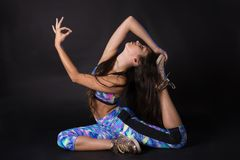 Portrait of young beautiful latin woman on its side doing a yoga pose Royalty Free Stock Image