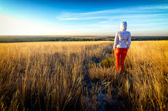 Young beautiful lean girl wears red pants and white hoodie stays in a field among golden grass at sunset, back to camera Royalty Free Stock Photos