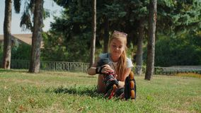 Young girl putting on her rollerblades sitting on grass. Young beautiful little girl sitting on the grass in a city park putting on her rollerblades - closing up stock video footage