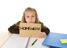 Young beautiful little schoolgirl sad and overwhelmed holding paper with the text homework. Written sitting at school desk in stress isolated on white Royalty Free Stock Images