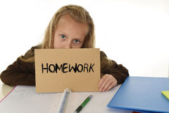 Young beautiful little schoolgirl sad and overwhelmed holding paper with the text homework. Written sitting at school desk in stress isolated on white Royalty Free Stock Photo