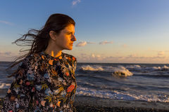 Young beautiful long hair woman on windy seashore Stock Photo