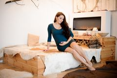 Young and beautiful long-haired pregnant woman sitting near the fireplace. Young and beautiful long-haired pregnant woman in a dress sitting near the burning Stock Photo