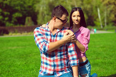 Young beautiful loving couple in checked shirts, jeans and sunglasses sitting on the green lawn. A boyfriend holding his girlfriend`s hand on his shoulder and royalty free stock photos