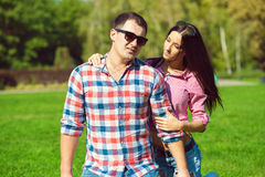 Young beautiful loving couple in checked shirts, jeans and sunglasses sitting on the green lawn. A girlfriend looking at her boyfriend with her hand on his stock image