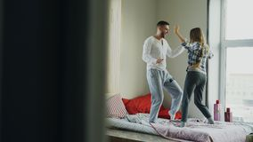 Young beautiful and loving couple dancing rocknroll dance on bed in the morning at home. Young beautiful and loving couple dancing rocknroll dance on bed in Stock Image