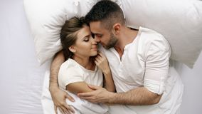 Young beautiful and loving couple kiss and hug into bed while waking up in the morning. Top view of attractive man Royalty Free Stock Photography