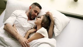 Young beautiful and loving couple talk and hug into bed while waking up in the morning. Top view of attractive man. Young beautiful and loving couple kiss and Royalty Free Stock Images
