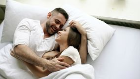 Young beautiful and loving couple talk and hug into bed while waking up in the morning. Top view of attractive man. Young beautiful and loving couple kiss and stock photography